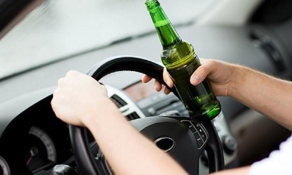 Полицейский ездит за рулем с бутылкой пива